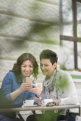 Two friends in the sidewalk cafe looking at phone, Bavaria, Germany