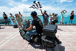 Jason Wadzinski riding Jess, his 1947 Indian Chief over the finish line of the Cross Country Chase motorcycle endurance run from Sault Sainte Marie, MI to Key West, FL. (for vintage bikes from 1930-1948). The Grand Finish in Key West's Mallory Square after the 110 mile Stage-10 ride from Miami to Key West, FL and after covering 2,368 miles of the Cross Country Chase. Sunday, September 15, 2019. Photography ©2019 Michael Lichter.