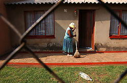 JOHANESBURG, SOUTH AFRICA - APRIL-28-2004 -&#xA;A woman sweeps her front porch in the Soweto Township of Johanesburg. The plastic bottle, which reflects the suns light, is left in the front yard top keep dogs away. (PHOTO © JOCK FISTICK)&#xA;&#xA;<br />