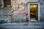 A woman walks past a grocers shop in the Old centre of Genoa, Italy. The heart of medieval Genoa is bounded by ancient city gates Porta dei Vacca and Porta Soprana, and the streets of Via Cairoli, Via Garibaldi and Via XXV Aprile and is famed for its caruggi narrow lanes.