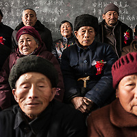 """Couples who have been married for 50 years or more pose for a group portrait on """"husband-and-wife day."""" These couples lived through the extreme depredations of the Great Leap Forward and the vicious repression of the Cultural Revolution."""