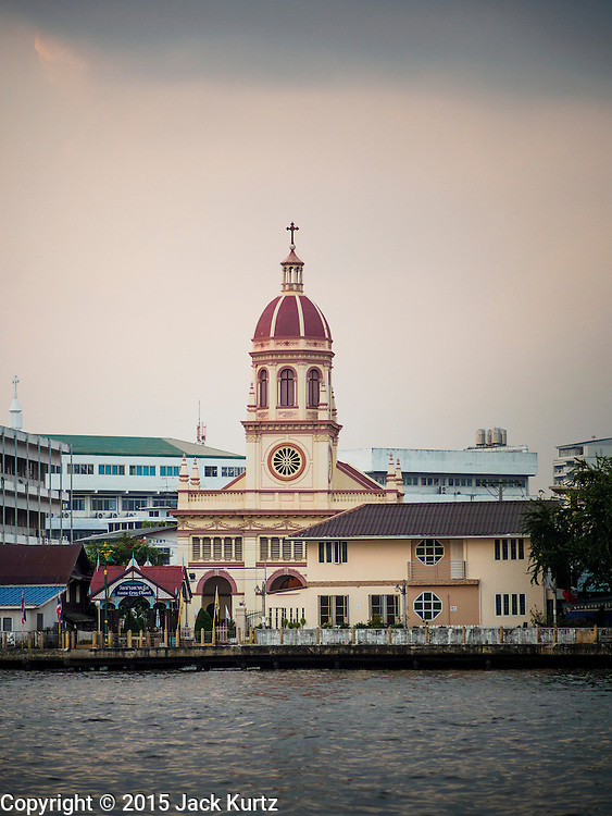 15 FEBRUARY 2015 - BANGKOK, THAILAND:  The spire of Santa Cruz Catholic Church towers over the Kudeejeen neighborhood in Bangkok. Santa Cruz church was established in 1770  and is one of the oldest and most historic Catholic churches in Thailand. The church was originally built by Portuguese soldiers allied with King Taksin the Great. Taksin authorized the church as a thanks to the Portuguese who assisted the Siamese during the war with Burma. Most of the Catholics in the neighborhood trace their family roots to the original Portuguese soldiers who married Siamese (Thai) women. There are about 300,000 Catholics in Thailand in about 430 Catholic parishes and about 660 Catholic priests in Thailand. Thais are tolerant of other religions and although Thailand is officially Buddhist, Catholics are allowed to freely practice and people who convert to Catholicism are not discriminated against.     PHOTO BY JACK KURTZ