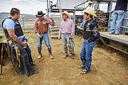 14 JULY 2012 - OAK SPRINGS, AZ: MONTE YAZZIE (3rd from left, turquoise rope), from the Crooked Horn Cattle Co, talks to student bull riders at the bull riding class in the Aspen Canyon Rodeo Club in Oak Springs Saturday. The bull riding class was offered by the Crooked Horn Cattle Co. in the community of Oak Springs on the Navajo Nation, about 15 miles south of Window Rock, AZ. Eleven cowboys signed up for bull riding classes and one signed up for bull fighting classes. The bull riding class started with lessons on a mechanical bucking machine before the cowboys rode bulls.    PHOTO BY JACK KURTZ
