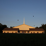 Hot air balloons pass the Faith Baptist church as they take to the skies around rural Michigan near Battle Creek during the World Hot Air Ballooning Championships. Battle Creek, Michigan, USA. 20th August 2012. Photo Tim Clayton