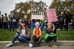 © Licensed to London News Pictures. 19/10/2020. London, UK. Bibi (11), Xavi (8) and Ramsey (9) wave placards and bang pans in Parliament Square as workers in the hospitality sector protest against the impact COVID-19 restrictions are having on the hospitality industry. Photo credit: Rob Pinney/LNP