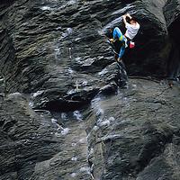 Man rock climbing on sea cliffs of Jogasaki, Japan