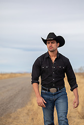 attractive cowboy walking on a dirt road