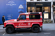 Christmasthemed red liveried Jeep 4x4 SUV on Bond Street exclusive shopping district on 1st December 2020 in London, United Kingdom. Bond Street is one of the principal streets in the West End shopping district and is very upmarket. It has been a fashionable shopping street since the 18th century. The rich and wealthy shop here mostly for high end fashion and jewellery.