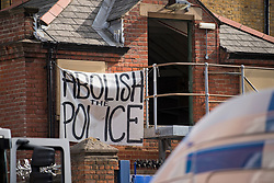 """© Licensed to London News Pictures. 29/03/2021. London, UK. A sign reading """"ABOLISH THE POLICE"""" hangs from the former Cavendish Road Police Station in Clapham in south London where squatters occupied the building as part of a 'Kill The Bill' protest. Murdered woman Sarah Everard walked past the building on the night she went missing on March 3, 2021. Photo credit: Ben Cawthra/LNP"""
