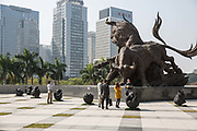 A group of visitors have their pictures taken in front of a bull statue at the Shenzhen Stock Exchange building in Shenzhen, China, on Wednesday, Dec. 16, 2015.