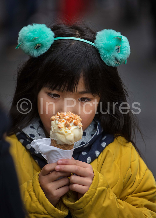 Young girl during the Chinese New Year celebrations about to eat an icecream cone on 26th January 2020, Soho London, United Kingdom. Londons Lunar New Year festivities welcome the Year of the Rat.