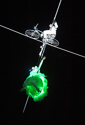 """© Licensed to London News Pictures.  24/01/2015. Bristol, UK.  """"Bridging the Gap"""", the launch of Bristol Green Capital 2015 at the Create Centre in Bristol.  Tight wire artist Jade Kindar-Martin cycled across a 120m high wire 27m above the ground between two warehouses (one of which is the Create Centre) with Hollywood stuntwoman Karine Mauffrey performing an aerial trapeze routine suspended beneath the bicycle. There were also other performers with led lit umbrellas, and singers.  Photo credit : Simon Chapman/LNP"""