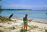 Expatriate tourist woman beachcomber walking along sandy beach by blue sea, island of Tobago,  1963