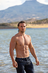 good looking man in wet jeans by a lake in New Mexico