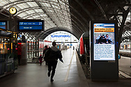 Berlin, Germany - September 6, 2015: A man runs down a platform at the Leipzig train station to catch a train about to leave for Dresden, Germany. To his right is an electronic board showing the news that Great Britian will take in 15,000 Syrian refugees.