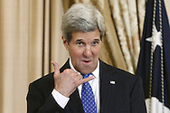 """U.S. Secretary of State John Kerry makes the """"call me"""" signal to someone in the audience as he plays host to a luncheon celebrating recipients of the Art in Embassies Medal of Arts Award at the State Department in Washington."""