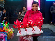 23 DECEMBER 2017 - HANOI, VIETNAM: A A woman sells Christmas themed antler hats at a holiday street fair in the old quarter of Hanoi. The commercial and gift giving aspect of Christmas is widely celebrated in Vietnam and Vietnam's 5+ million Catholics celebrate the religious aspects of Christmas.     PHOTO BY JACK KURTZ