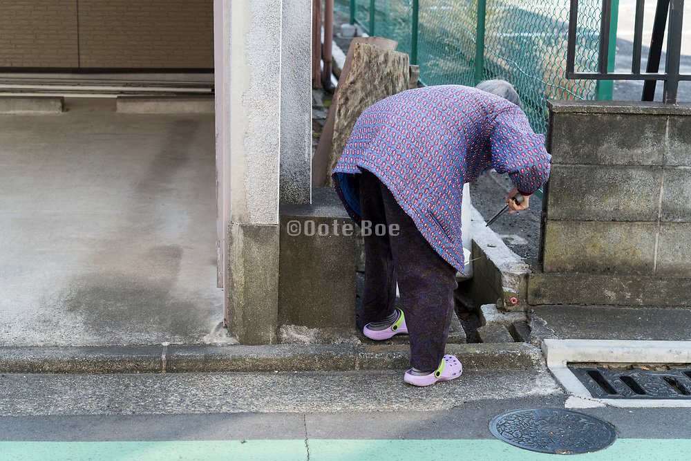 elderly woman cleaning the roadside rainwater drainage Yokosuka Japan