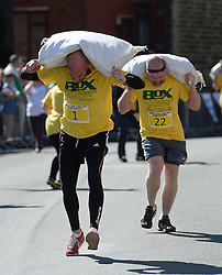 © Licensed to London News Pictures. 06/04/2015. Gawthorpe, UK. Competitor John Gibbons approaches the finish line before falling during the World Coal Carrying Championships, Gawthorpe, West Yorkshire. Photo credit : Anna Gowthorpe/LNP