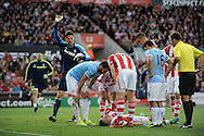 players show their concern  for Stoke's Robert Huth as he lies flat out motionless after a collision with Man city's Alvaro Negredo during the Barclays Premier league match, Stoke city v Manchester city at the Britannia Stadium in Stoke on Trent on Sat 14th Sept 2013. pic by Jeff Thomas, Andrew Orchard sports photography,