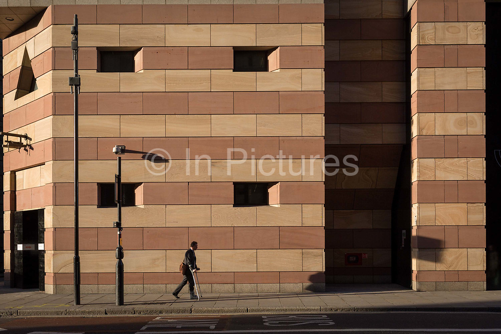 A man hobbles on crutches beneath the modern architecture of One Poultry, on 30th October 2017, Queen Victoria Street, City of London, England.
