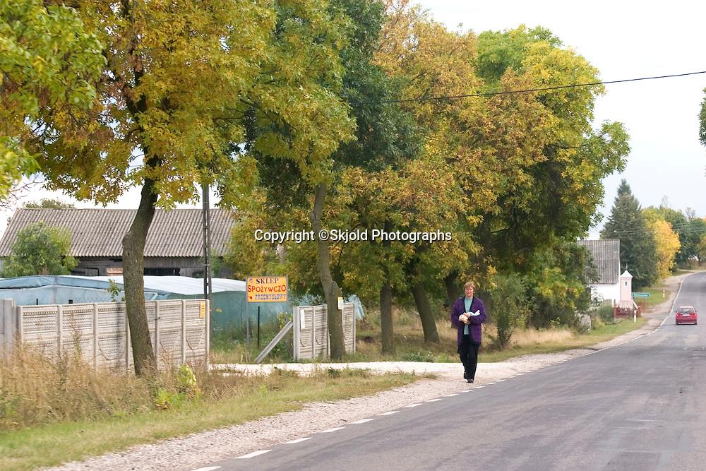 Woman walking along the road. Rawa Mazowiecka Central Poland
