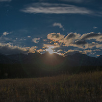 The moon lights clouds over the Canadian Rockies in Banff National Park, Alberta, Canada.