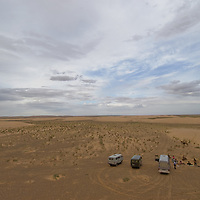 Vans, camels and traders await a geo tourism group trekking in sand dunes in the southern Gobi Desert.