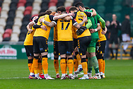 Newport players huddle together before the start of the The FA Cup match between Newport County and Salford City at Rodney Parade, Newport, Wales on 28 November 2020.