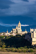 Famous view of Alcazar Castle - palace and fortress which inspired Disney castle, Cathedral and dramatic sky in Segovia, Spain