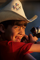Stock photo of a young boy in a cowboy hat at sunset