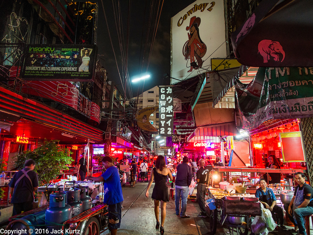 "03 NOVEMBER 2016 - BANGKOK, THAILAND: A woman wearing a black mourning dress walks to work on ""Soi Cowboy,"" one of Bangkok's best known ""adult entertainment districts."" Bangkok's infamous nightlife has been scaled back during the mourning period for the late Bhumibol Adulyadej, King of Thailand. The revered King died on 13 October 2016 at age 88. The government declared a year of mourning. The government ordered Thailand's notorious adult entertainment districts to turn off their neon lights, dress employees in black and ensure that music can't be heard on the street in front of the venues for 30 days, the government said the entertainment venues could resume normal operations on 14 November.        PHOTO BY JACK KURTZ"