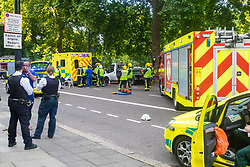 London, July 7th 2017. Emergency services attend a collision between a red Toyota Prius and an ambulance on Park Lane at the intersection of Upper Grosvenor Street. There are no reported injuries, but the ambulance was carrying a patient at the time of the collision, which has closed down all but one southbound lane on Park Lane, with surrounding streets closed to traffic. PICTURED: A General view of the scene with the stricken ambulance with damage to its back end.