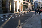With most Londoners still working from home, a lone commuter walks on a widened Old Board Street pavement at evening rush-hour during the third lockdown of the Coronavirus in the City of London, the capital's financial district, on 26th February 2021, in London, England.
