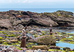 Dunbar, , Scotland, United Kingdom 10 July 2021. European Stone Stacking Championship: The first day of the event, which is part of the Edinburgh Science Festival.  Pictured: A girl watches from the rocks in the bay.<br /> Sally Anderson | EdinburghElitemedia.co.uk