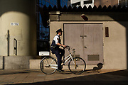 A Japanese police officer rides a bicycle under the Shuto expressway overpasses in Edogawabashi, Tokyo, Japan Friday April 20th 2018