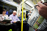 London Underground passengers on a Circle Line tube train reading free newspapers like the Evening Standard.