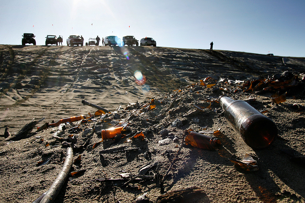 """Members of the Tri-Cities based Peak Putters and Yakima based All Wheelers off road clubs take a break at the top of a hill overlooking an old campsite full of debris and beer bottles. Club members not only dislike the danger of driving over glass and nails leftover from pallet fires, but also being lumped in with the offenders, who they often attribute as partying high school kids. The group packs out whatever it brings in, plus other garbage they find on the site. """"It's public land,"""" says Dave Walters. """"It's here for everybody, but you have to treat it right."""""""