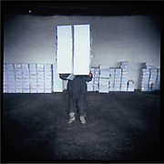 A boy carries boxes at a factory outside of Kabul.