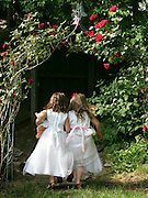 Two best friends enjoy time playing dress- ups and playing in the garden. (Model Released)