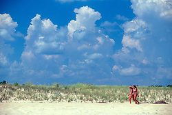 Unidentified women are framed by dramatic clouds as they prowl the beach at North Shores, Monday, Aug. 19, 2019 in Rehoboth Beach, Del. (Photo by D. Ross Cameron)