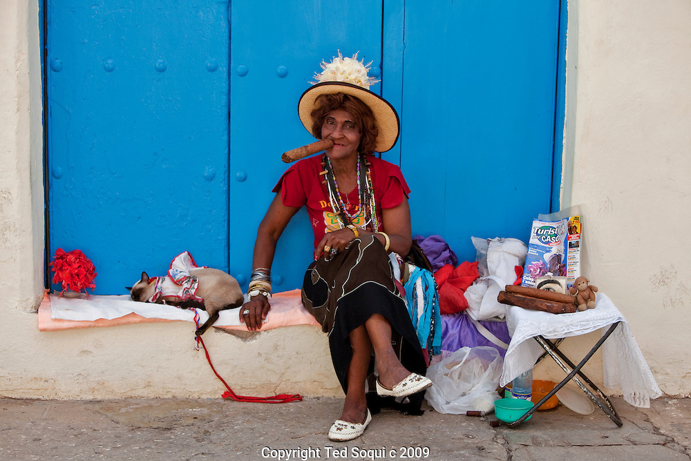 A old woman poses for tourist holding a huge cigar, she usually charges one Cuba peso for a photo. There are several woman around old Havana that do this for a living.