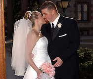 """Newlyweds Alison Anne Reitter and Michael Orlando kissing in the doorway of The University Church on the campus of Fordham University in the Bronx, NY after their wedding ceremony on Saturday, March 15, 2003.  Quote from the Best Man, Christopher Orlando: """" Michael and Alison are soulmates, not one created on TV or made over a couple of weeks. Their relationship is built to last."""" (Photograph by Chet Gordon for The New York Daily News)"""