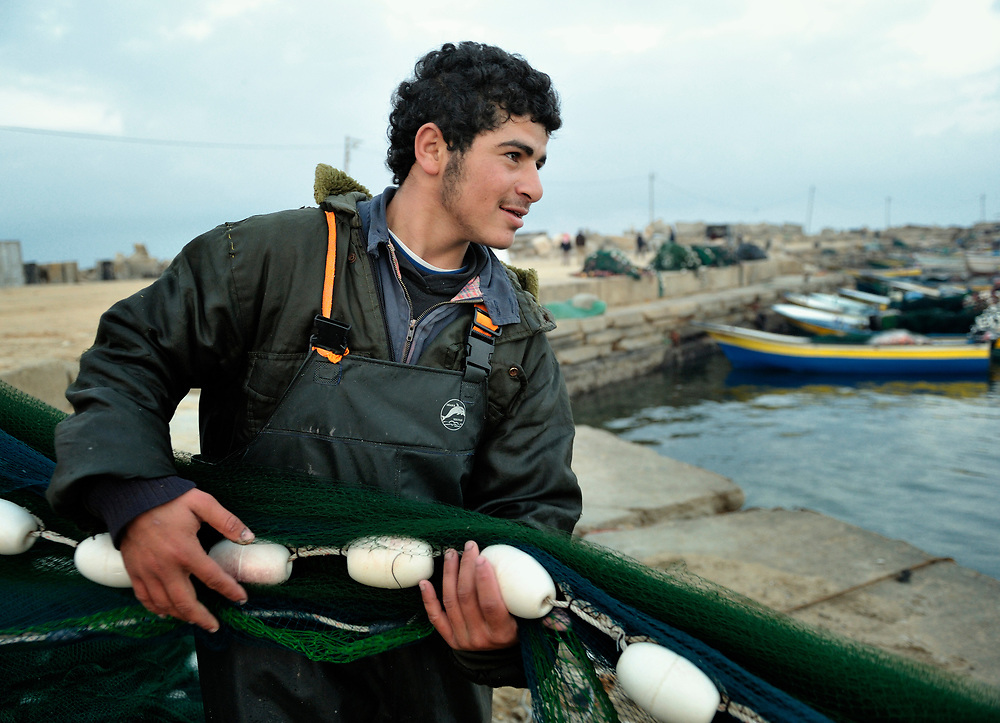 A fisherman pulls in a net at the dock in Gaza City. Under the 1993 Oslo Peace Accords, the people of the Gaza Strip were allowed to fish out to 20 nautical miles from their coastline, yet since the Israeli military imposed a naval blockade in 2007 they have been limited to just three nautical miles. In practice, fishers who venture beyond two nautical miles are shot at by Israeli gunboats; several have been injured and some killed. Despite having 40 kilometers of coastline and a long tradition as fishers, many fishers are unemployed and the people of Gaza are forced to import fish from Israel. And what fishing they can do close to shore mostly involves the harvest of immature fish, which biologists warn has a negative impact on fish stocks in the region....