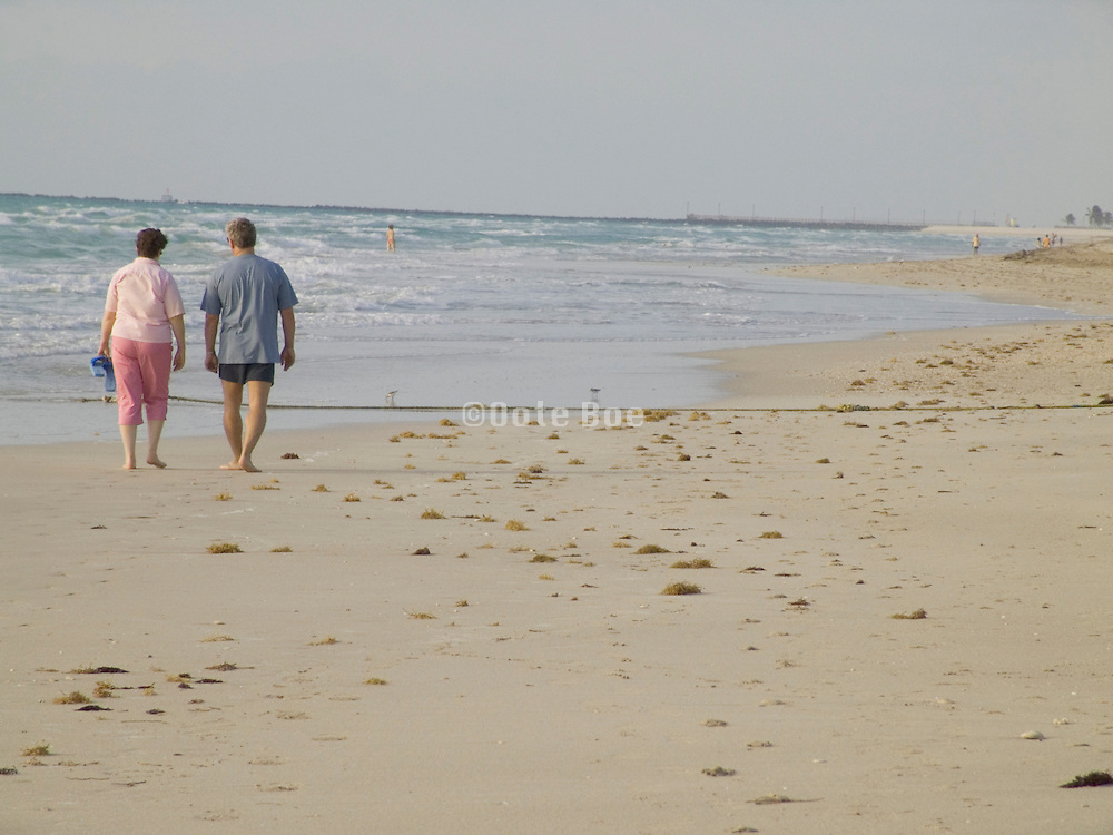 couple walking in the early morning along the beach Miami Beach USA