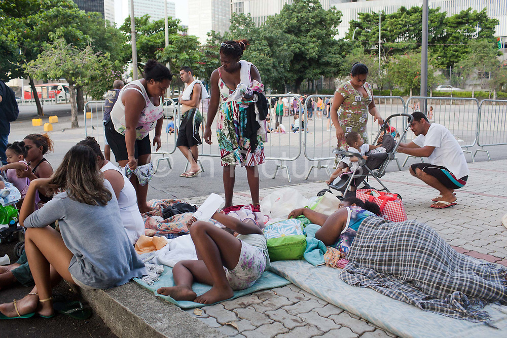 People lying down and sleeping on the floor. In April 2014 thousands of people were evicted from Telerj favela in an old building owned by communications company Oi. Having nowhere to go, they camped outside the Central Cathderal in Rio de Janeiro, Brazil. Many of them were children, they received many donations from local people and community groups.