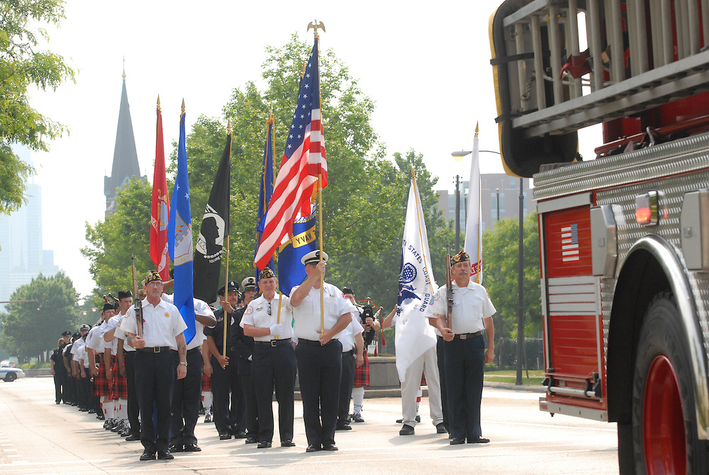 Chicago Fire Department personnel are gathered on W. Roosevelt Road to commemorate the service of fallen colleagues and military veterans during a procession to begin a Memorial Day mass at Holy Family Church.