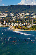 View of West Vancouver, the beach at Ambleside Park, and waves on English Bay during a stormy fall afternoon.  Photographed from Stanley Park's Prospect Point in Vancouver, British Columbia, Canada.
