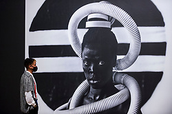 """© Licensed to London News Pictures. 03/11/2020. LONDON, UK. A staff member views a self-portrait """"Sebenzile, Parktown"""", 2016, by Zanele Muholi. Preview of the first major UK exhibition by South African visual activist Zanele Muholi at Tate Modern.  260 photographs document black lesbian, gay, trans, queer and intersex lives in South Africa.  The show runs 5 November to 7 March 2021, but will be interrupted by England's coronavirus pandemic lockdown currently due to last 5 November to 2 December.   Photo credit: Stephen Chung/LNP"""