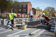 A group of builders use trowels to lay the first bricks with cement onto the foundations on new house construction site in Norwich. Norfolk. United Kingdom